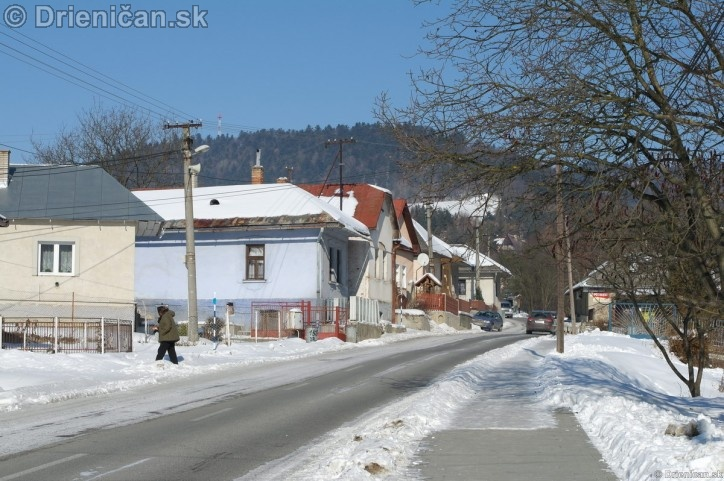 Hlavná cesta prechádzajúca hornou časťou obce, napravo zasnežený chodník.