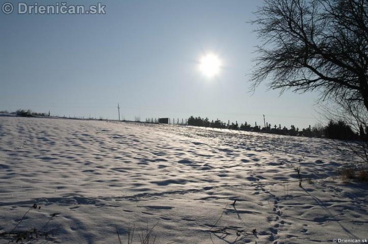 Zasnežené pole, napravo cintorín.